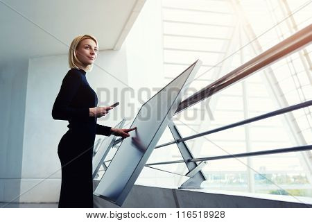Elegant female holding mobile phone while standing front high tech digital device in office interior