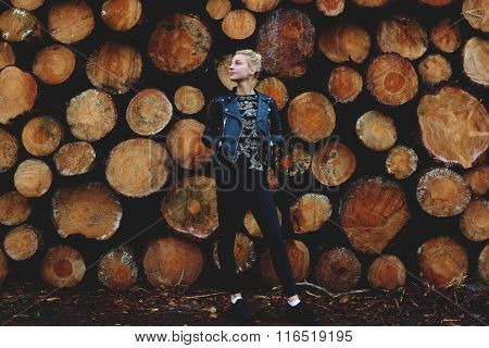 Thoughtful young woman enjoying fresh air while standing outside near stacked wooden cut logs