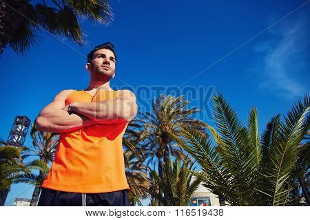 Young sportsman with crossed arms resting outdoors after physical exercise in summer season