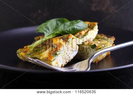 Baked Omelette With Spinach In A Black Plate On A Dark Background