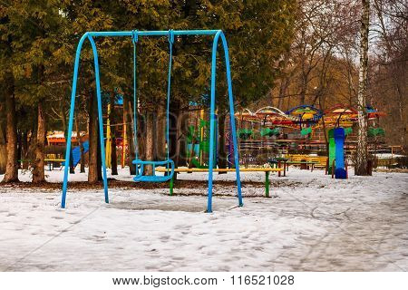 Empty Blue Swing And Children Playground In Winter Park, Outdoors