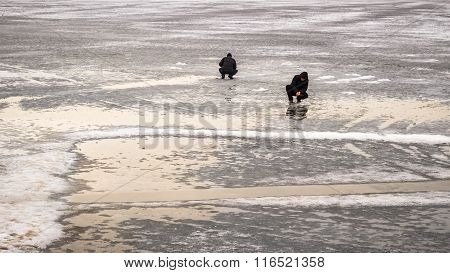 Two Fisherman On Winter Fishing On The Thin Ice River