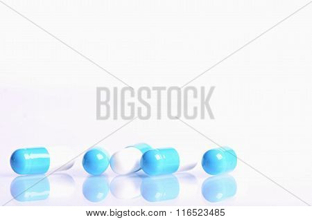 Tablets isolated on a white background. Reflection of pills on a glass. Medicine´s background.