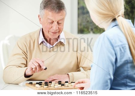 Senior Man Playing Checkers With Teenage Daughter