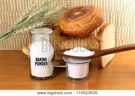 baking powder in a glass jar and wooden spoon with cookie and bread and wheat