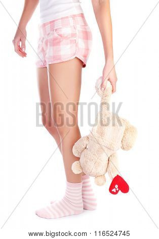 Young girl holding in hand soft bear toy with heart isolated on white background, body part, unhappy love concept