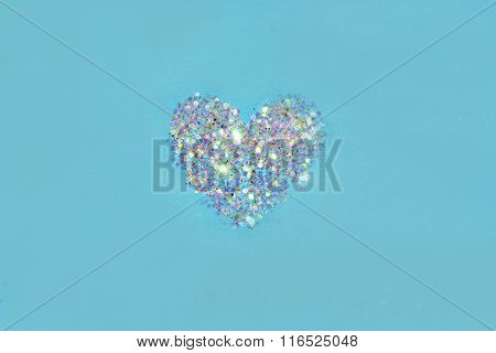 Abstract heart of white glitter sparkle on blue background