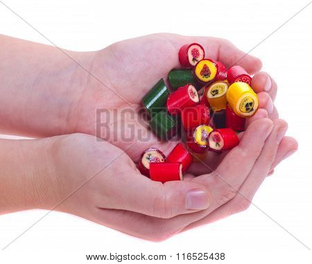 Many Caramel Colored Candies With Cool Designs In Hands Isolated White