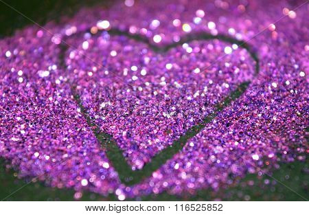 Blurry abstract background with heart of purple glitter on black surface