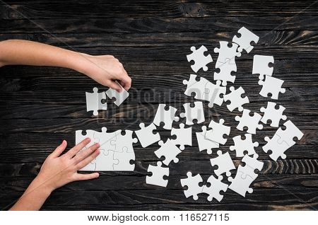 hands starting to collect puzzle pieces