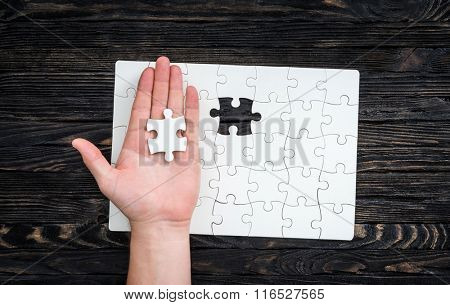 hand with the last piece of white uncomleted puzzle