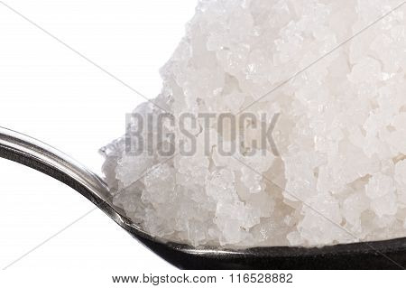 Sea salt crystals large in spoon macro. Side view.