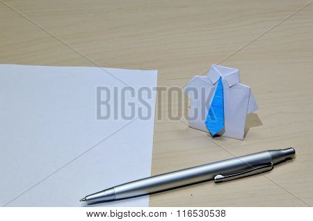 Close up photo of origami suit with blue tie near paper and pen on desk