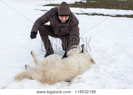 Man Playing With A White Dog In Winter
