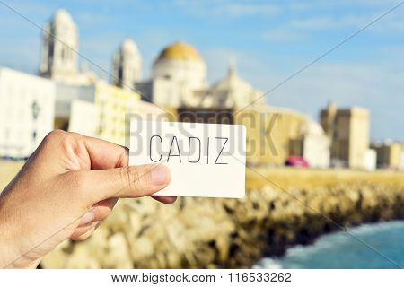 closeup of the hand of a young man showing a signboard with the word Cadiz, in the city of Cadiz, Spain, bordered by the Mediterranean sea and its Cathedral in the background
