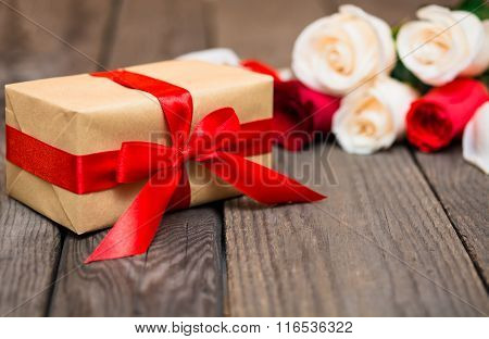 Gift Box With Blured Red And White Roses On A Dark Wooden Background. Women' S Day, Valentines Day,