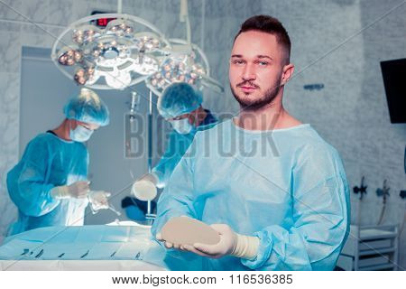 Team surgeon at work in operating room. breast augmentation.