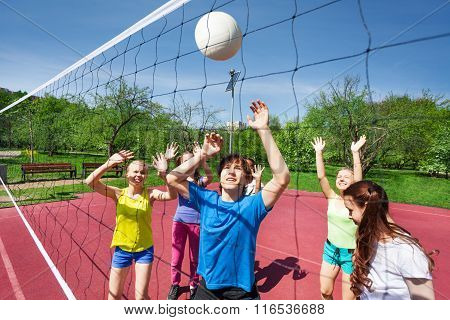 Teens in motion with arms up try to catch ball