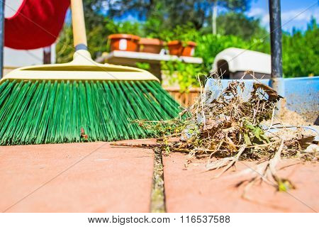 Grass And Broom On A Red Floor