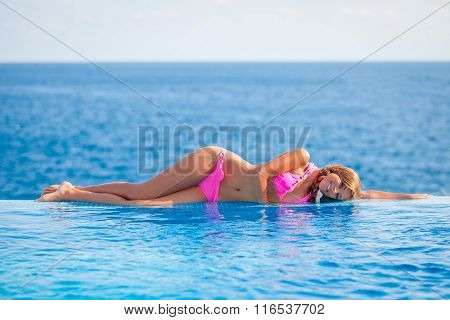 summer woman sunbathing in infinity pool in Mallorca or Majorca