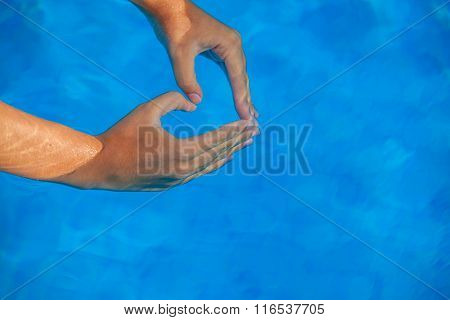summer vacation love heart shaped hands in pool.