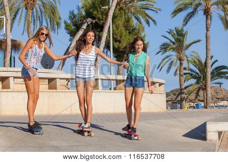 happy girls having fun on skateboards on holiday in Magalluf Mallorca