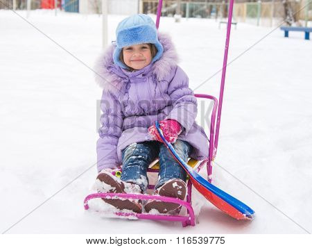 Joyful Girl Sitting On A Sled In The Snowy Weather