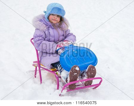 Joyful Girl Sitting On A Sled