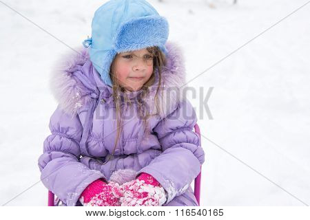 Tired Girl Sitting On A Sled