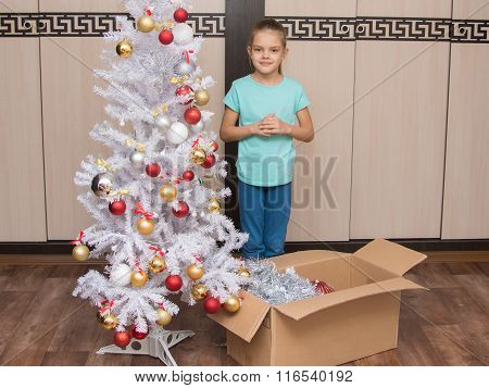 Seven-year Girl Stands In A Box With Christmas Toys And Christmas Tree