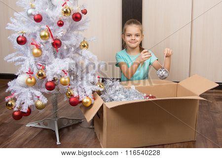 Happy Christmas Girl Puts The Ball Into The Box