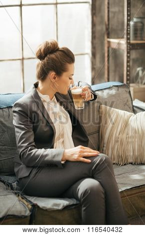 Business Woman Sitting On Sofa And Drinking Coffee In Loft