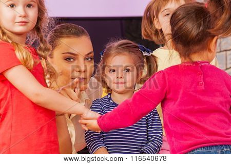 Teacher show little girl pointing finger in group