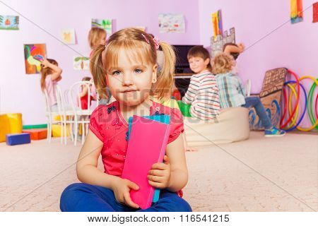 Little girl with book in the class