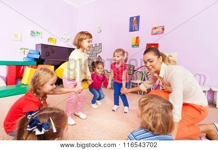 Little children boys, girls squat play roundelay