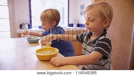 Couple Of Cute Young Boys Eating Breakfast Together