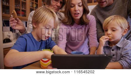 Closeup Of A Beautiful Caucasian Famly Enjoying Cookies While Watching An Ebook