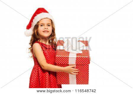 Close portrait of girl in Santa hat hold present