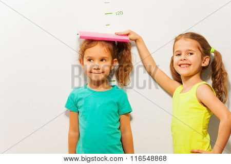 Two girls standing by the scale on the wall and fixating the height with book looking at camera and smiling