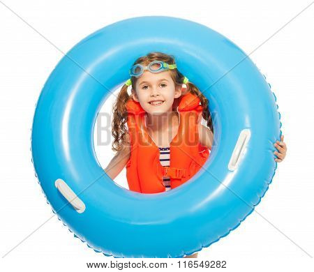 A girl in lifejacket and goggles with rubber ring