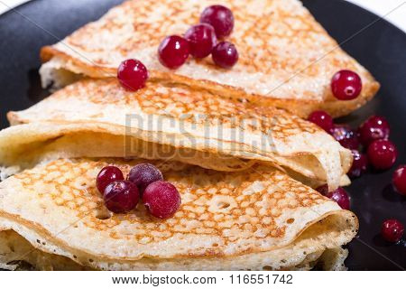 Fragment Of A Pile Of Pancakes On A Black Plate With Red Berries Of A Cranberry