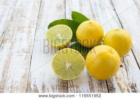 Freshly Cut Half And Whole Lemons On White Wooden Table