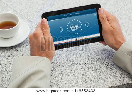 Businessman holding small tablet at table against web
