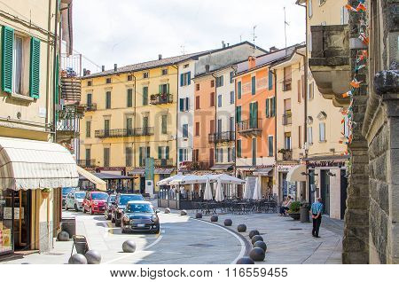 Porretta Terme, Italy - August 2, 2015 - Colorful Buildings, Parked Cars And People Walking In The T