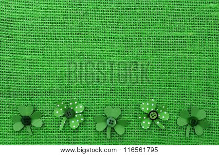 St Patricks Day border of paper shamrocks on green burlap