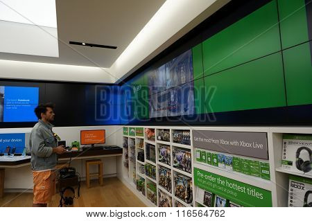 Man Stands Holding Controller Plays  Xbox One Inside Microsoft Windows Store