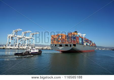 Fully Loaded Shipping Cargo Boat Pushed Through Harbor Under Giants Unloading Cranes