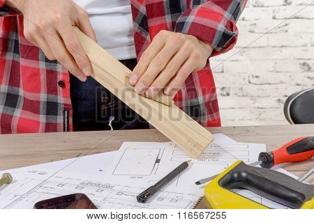 Young Carpenter Sanding A Wooden Board