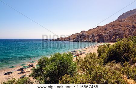 People having rest on sandy beach of Plakias town at Crete island.