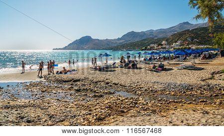 People having rest on sandy beach of Plakias town at Crete island